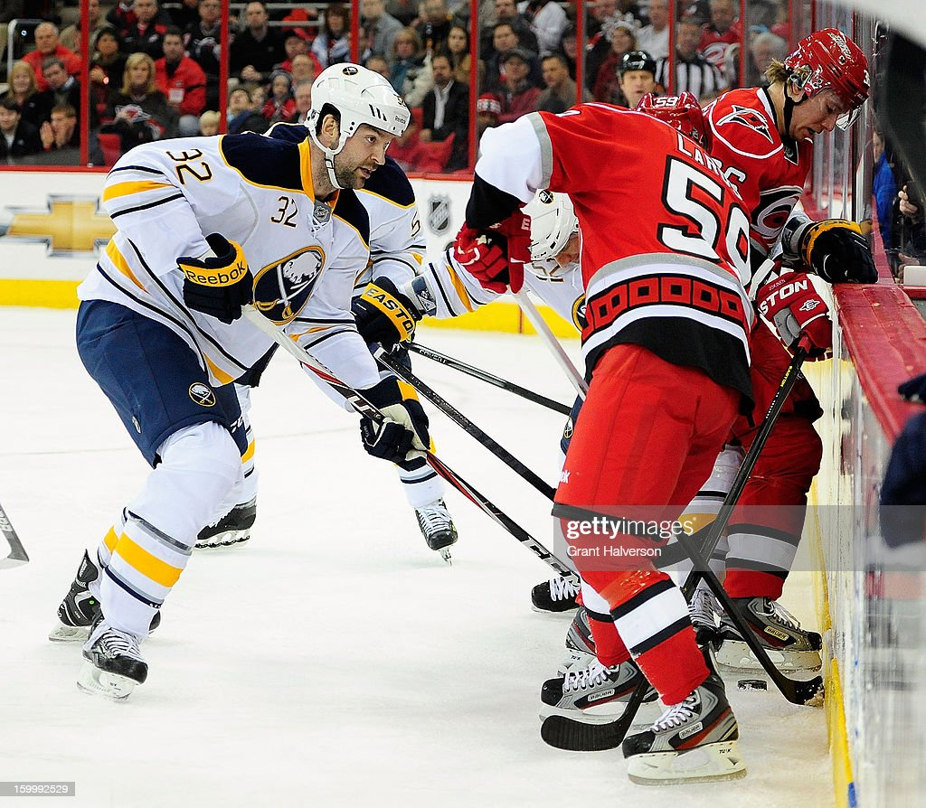 Chad LaRose #59 and Jussi Jokinen #36 of the Carolina Hurricanes battle for a puck along the boards with John Scott #32 of the Buffalo Sabres during play at PNC Arena on January 24, 2013 in Raleigh, North Carolina.