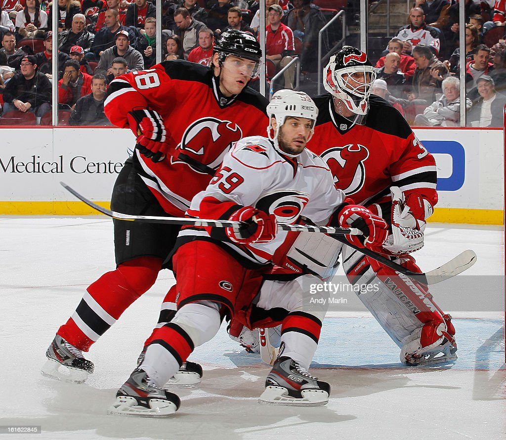 Chad LaRose #59 of the Carolina Hurricanes Anton Volchenkov #28 and Martin Brodeur #30 of the New Jersey Devils follow the puck during the game at the Prudential Center on February 12, 2013 in Newark, New Jersey.