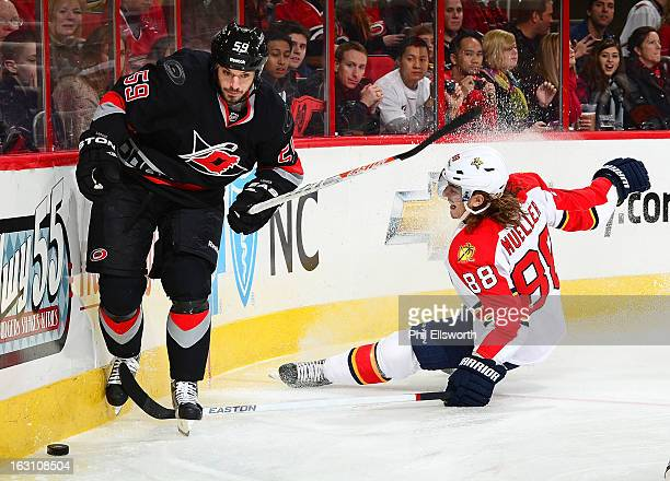 Chad LaRose of the Carolina Hurricanes avoids the hit from Peter Mueller of the Florida Panthers during an NHL game on March 2 2013 at PNC Arena in...