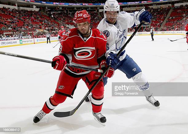 Chad LaRose of the Carolina Hurricanes battles for position in the corner with Teddy Purcell of the Tampa Bay Lightning during their NHL game at PNC...