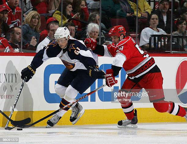 Chad LaRose of the Carolina Hurricanes battles for the puck along the boards with Maxim Afinogenov of the Atlanta Thrashers during their NHL game on...