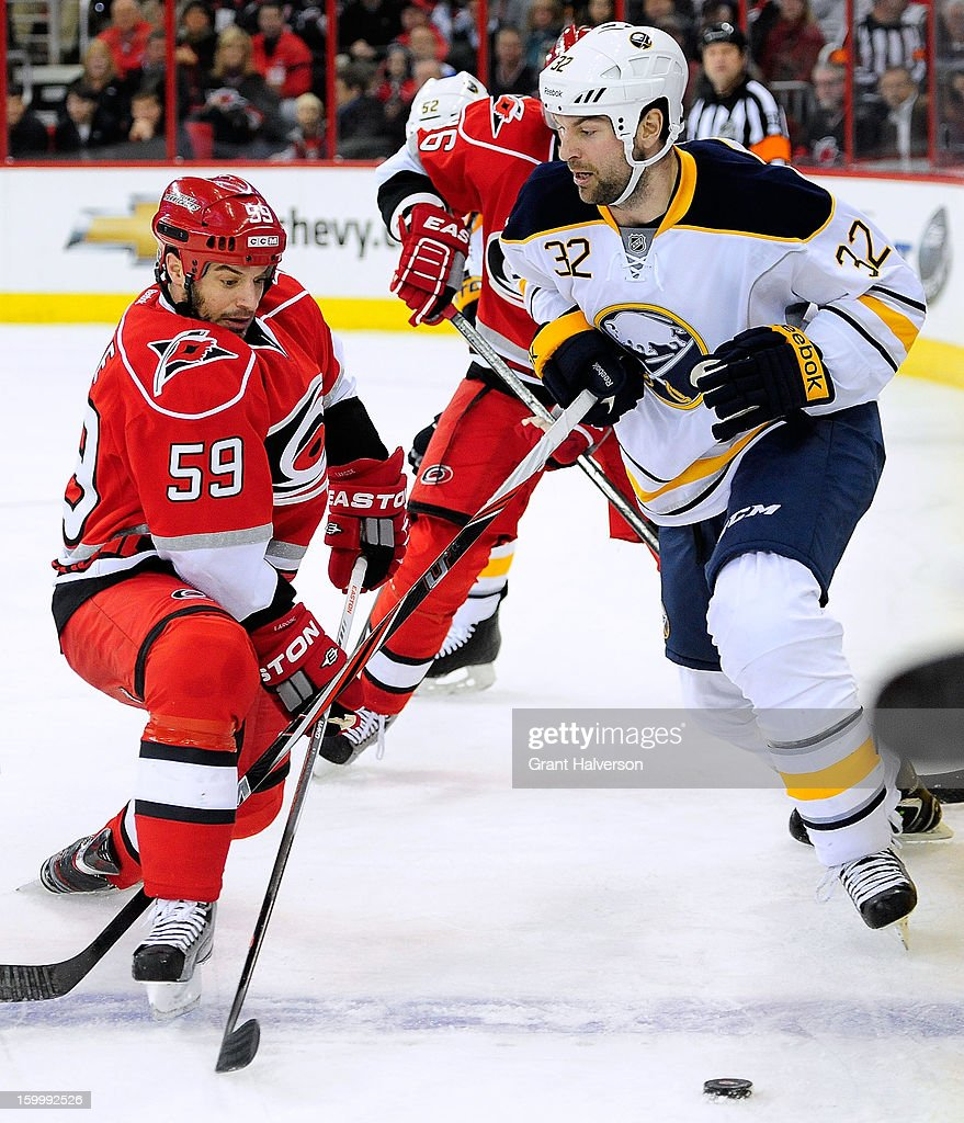 Chad LaRose #59 of the Carolina Hurricanes battles for the puck with John Scott #32 of the Buffalo Sabres during play at PNC Arena on January 24, 2013 in Raleigh, North Carolina.