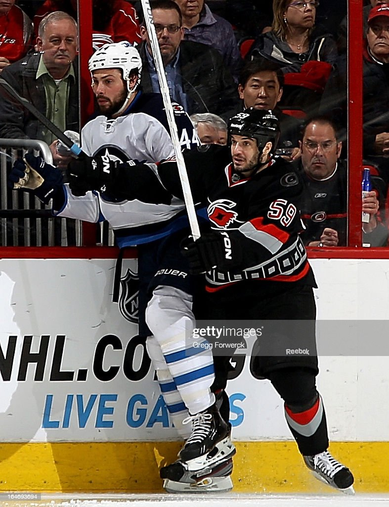 Chad LaRose #59 of the Carolina Hurricanes checks Zach Bogosian #44 of the Winnipeg Jets during their NHL game at PNC Arena on March 26, 2013 in Raleigh, North Carolina. LaRose is returns to the lineup tonight after missing the team's last 10 games with a concussion.