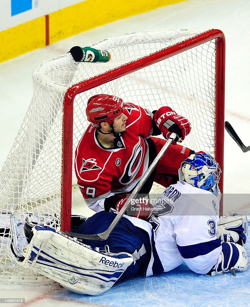 <a gi-track='captionPersonalityLinkClicked' href=/galleries/search?phrase=Chad+LaRose&family=editorial&specificpeople=546026 ng-click='$event.stopPropagation()'>Chad LaRose</a> #59 of the Carolina Hurricanes crashes into goaltender <a gi-track='captionPersonalityLinkClicked' href=/galleries/search?phrase=Mathieu+Garon&family=editorial&specificpeople=206119 ng-click='$event.stopPropagation()'>Mathieu Garon</a> #32 of the Tampa Bay Lightning during play at the RBC Center on March 3, 2012 in Raleigh, North Carolina. The Lightning won 4-3 in overtime.