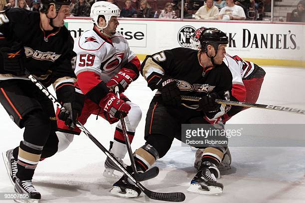Chad LaRose of the Carolina Hurricanes defends against Kyle Calder and Todd Marchant of the Anaheim Ducks during the game on November 25 2009 at...