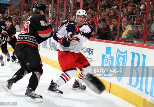 Chad LaRose of the Carolina Hurricanes defends Sami Lepisto of the Columbus Blue Jackets as he shoots the puck during an NHL game on March 12 2011 at...