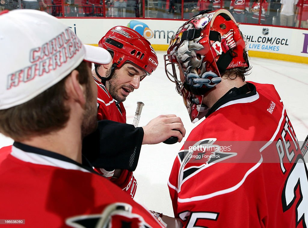 Chad LaRose #59 of the Carolina Hurricanes hands goaltender Justin Peters #35 the game puck as Dan Ellis waits to congratulate him following the team's victory over the Boston Bruins at PNC Arena on April 13, 2013 in Raleigh, North Carolina.