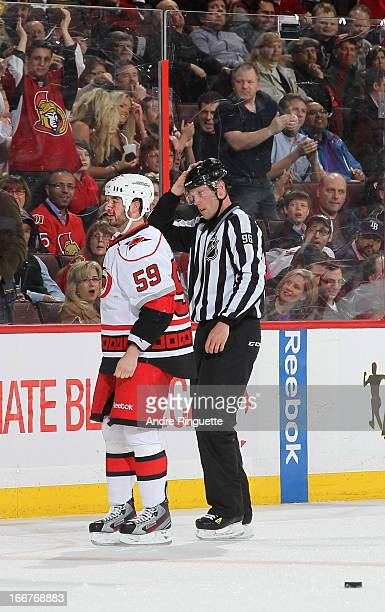 Chad LaRose of the Carolina Hurricanes is escorted to the penalty box by linesman David Brisebois after first period a fight in a game against the...