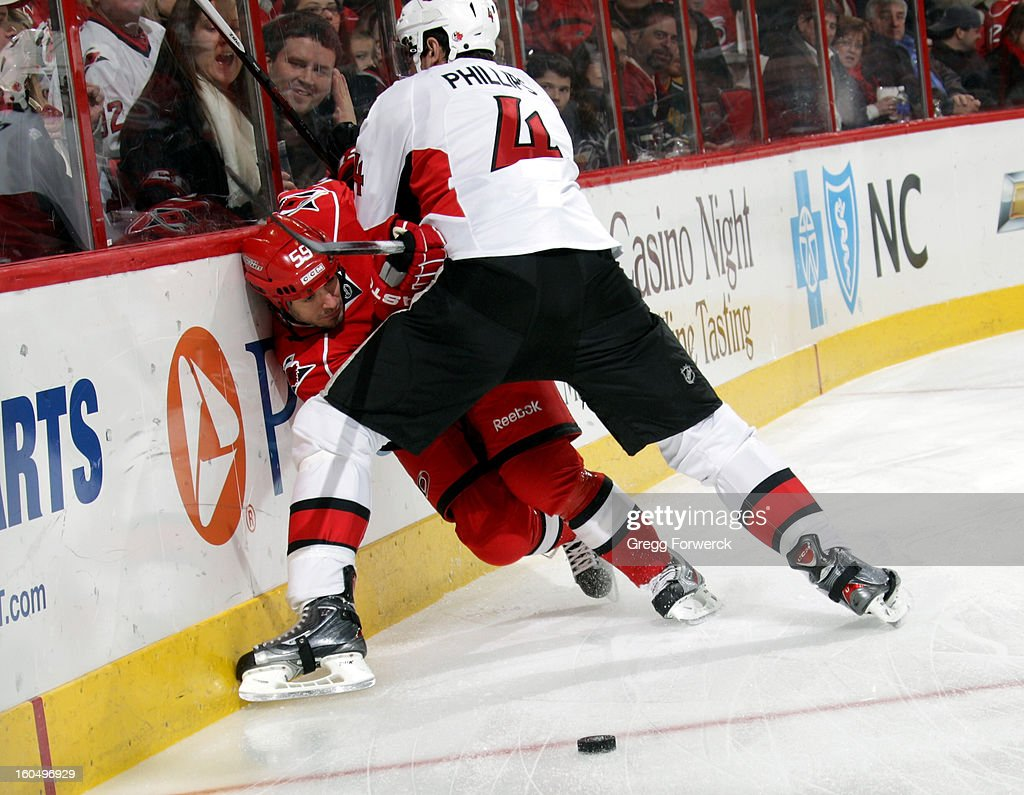 Chad LaRose #59 of the Carolina Hurricanes is knocked off the puck following a check from Chris Phillips #4 of the Ottawa Senators during their NHL game at PNC Arena on February 1, 2013 in Raleigh, North Carolina.