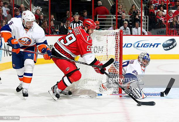 Chad LaRose of the Carolina Hurricanes is stick checked by Jesse Joensuu of the New York Islanders as he wraps the puck around to the front of the...