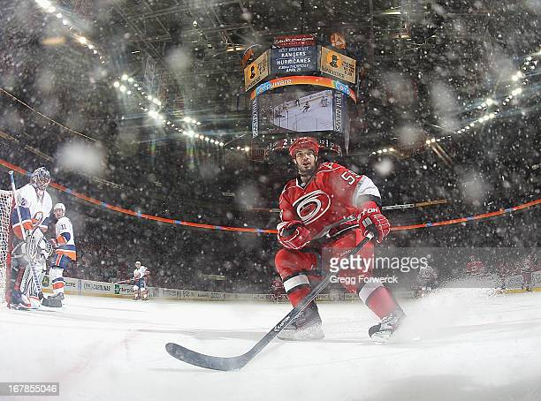 Chad LaRose of the Carolina Hurricanes looks to play a puck along the boards in the offensive zone of the during their NHL game against the NEw York...