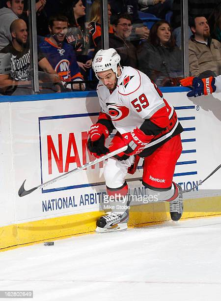 Chad LaRose of the Carolina Hurricanes skates the puck against the New York Islanders at Nassau Veterans Memorial Coliseum on February 24 2013 in...