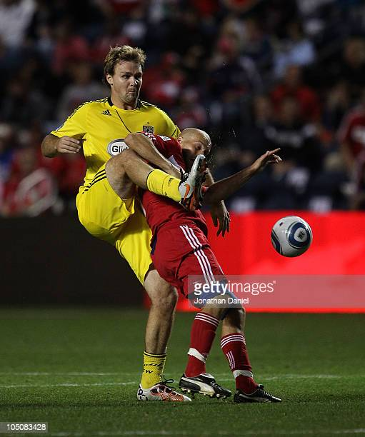 Chad Marshall of the Columbus kicks the ball away from Freddie Ljungberg of the Chicago Fire in an MLS match on October 8 2010 at Toyota Park in...