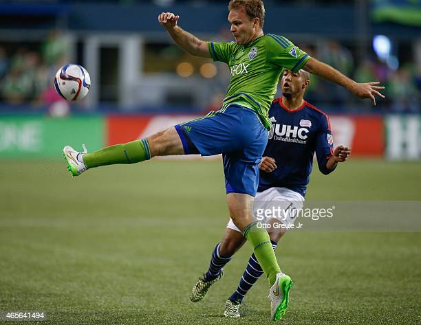 Chad Marshall of the Seattle Sounders FC passes against Teal Bunbury of the New England Revolution at CenturyLink Field on March 8 2015 in Seattle...