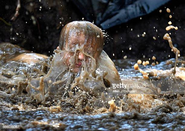 Chad Merriman of Garden Grove emerges from a plunge into the cool muddy waters after sliding down a mudslide at Adventure Playground in Huntington...