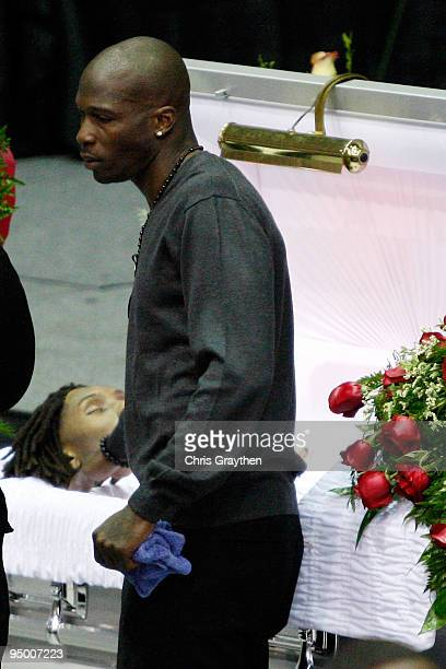 Chad Ochocinco of the Cincinnati Bengals stands over the open casket during the funeral for Cincinnati Bengals Player Chris Henry at the Alario...
