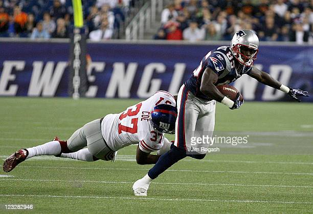 Chad Ochocinco of the New England Patriots gains yards against Michael Coe of the New York Giants at Gillette Stadium on September 1 2011 in Foxboro...