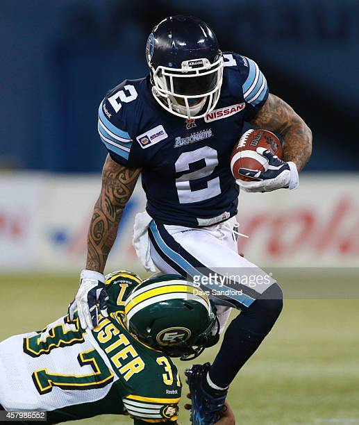 Chad Owens of the Toronto Argonauts as he is tackled by Otha Foster of the Edmonton Eskimos during their game at Rogers Centre on October 4 2014 in...