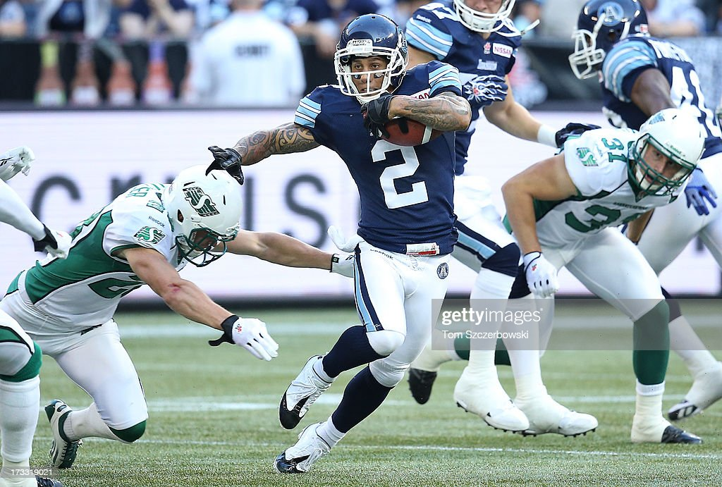 Chad Owens #2 of the Toronto Argonauts breaks a tackle as he runs with the ball during CFL game action against the Saskatchewan Roughriders on July 11, 2013 at Rogers Centre in Toronto, Ontario, Canada.
