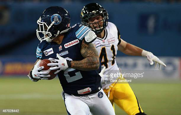 Chad Owens of the Toronto Argonauts runs in the winning touchdown as Erik Harris of the Hamilton TigerCats runs after him during their game at Rogers...
