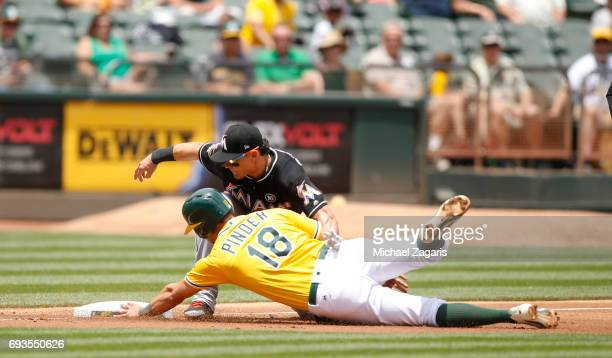 Chad Pinder of the Oakland Athletics beats the tag at second by Derek Dietrich of the Miami Marlins during the game at the Oakland Alameda Coliseum...
