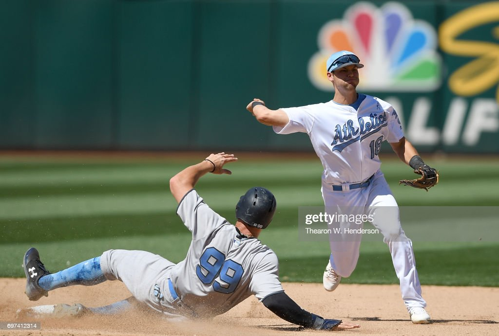 Chad Pinder #18 of the Oakland Athletics completes the double-play throwing over the top of Aaron Judge #99 of the New York Yankees in the top of the eighth inning at Oakland Alameda Coliseum on June 18, 2017 in Oakland, California.