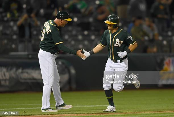 Chad Pinder of the Oakland Athletics is congratulated by third base coach Steve Scarsone after Pinder hit a solo home run against the Houston Astros...
