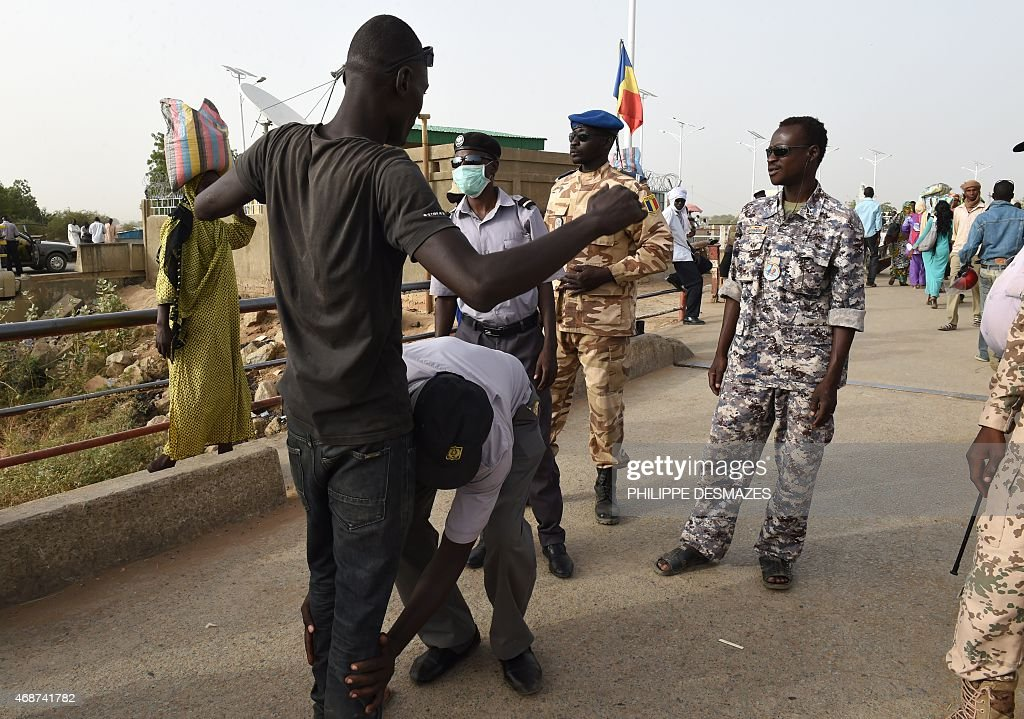 Chad police officers control people on April 4 2015 on the N'Gueli bridge marking the border between Chad and Cameroon near N'Djamena N'Gueli bridge...