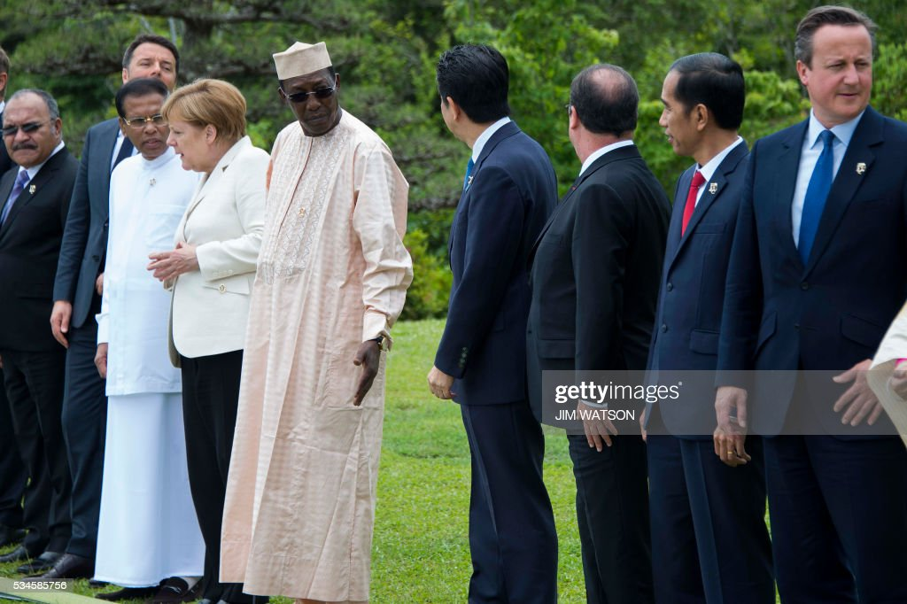 Chad President Idriss Deby Itno (5th L) gestures to US President Barack Obama's empty place as he speaks with Japanese Prime Minister Shinzo Abe (4th R) at the 'Outreach Session' family photo at the G7 Summit in Shima in Mie prefecture on May 27, 2016. A British secession from the European Union in next month's referendum could have disastrous economic consequences, G7 leaders warned on May 27 at the close of the summit in Japan. / AFP / POOL / JIM