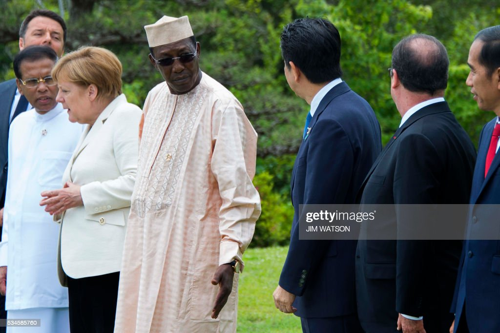 Chad President Idriss Deby Itno (4th L) gestures to US President Barack Obama's empty place as he speaks with Japanese Prime Minister Shinzo Abe (3rd R) at the 'Outreach Session' family photo at the G7 Summit in Shima in Mie prefecture on May 27, 2016. A British secession from the European Union in next month's referendum could have disastrous economic consequences, G7 leaders warned on May 27 at the close of the summit in Japan. / AFP / POOL / JIM