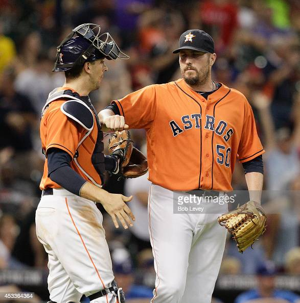 Chad Qualls of the Houston Astros taps the chest protector of Jason Castro after the final out against the Texas Rangers at Minute Maid Park on...