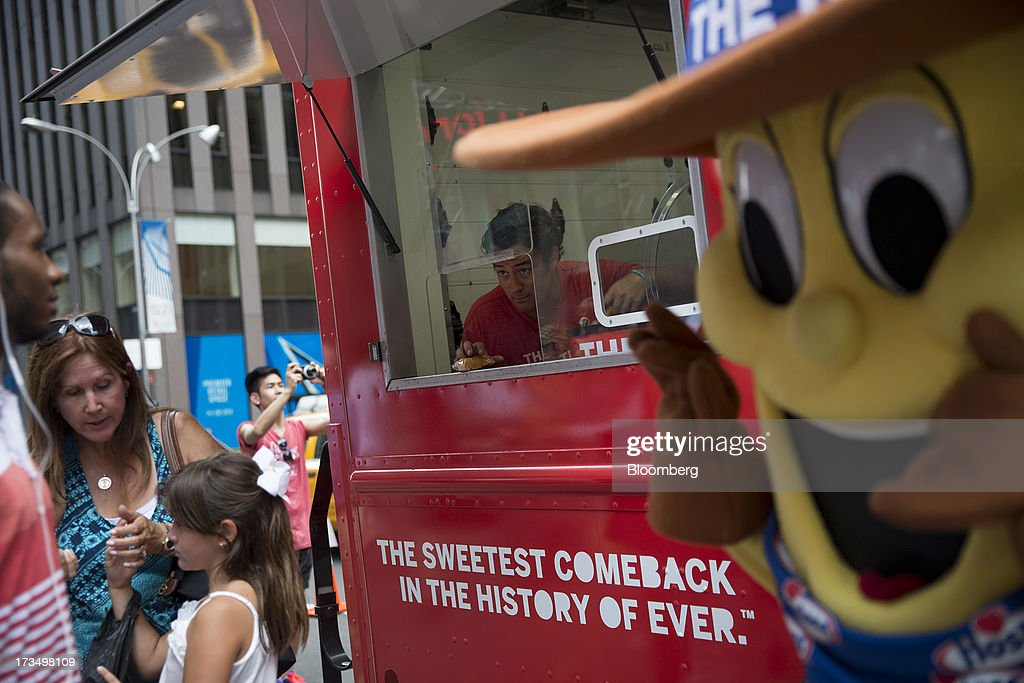 Chad Reinhart hands out Hostess Brands LLC Twinkies snack cakes to passersby as part of a promotion in New York, U.S., on Monday, July 15, 2013. Hostess Brands LLC officially revives sales of the iconic Twinkie snack cake today, following a seven-month hiatus after the original company decided to liquidate under bankruptcy. Photographer: Scott Eells/Bloomberg via Getty Images