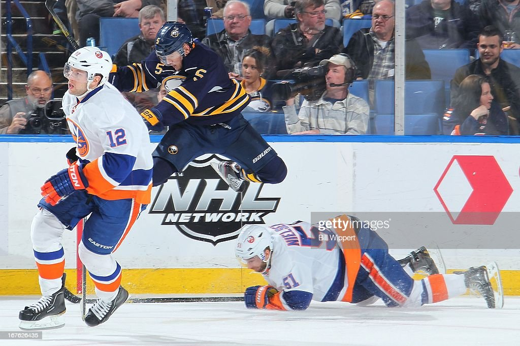 Chad Ruhwedel #5 of the Buffalo Sabres leaps over Frans Nielsen #51 of the New York Islanders alongside Josh Bailey #12 on April 26, 2013 at the First Niagara Center in Buffalo, New York. The Sabres defeated the Islanders 2-1.
