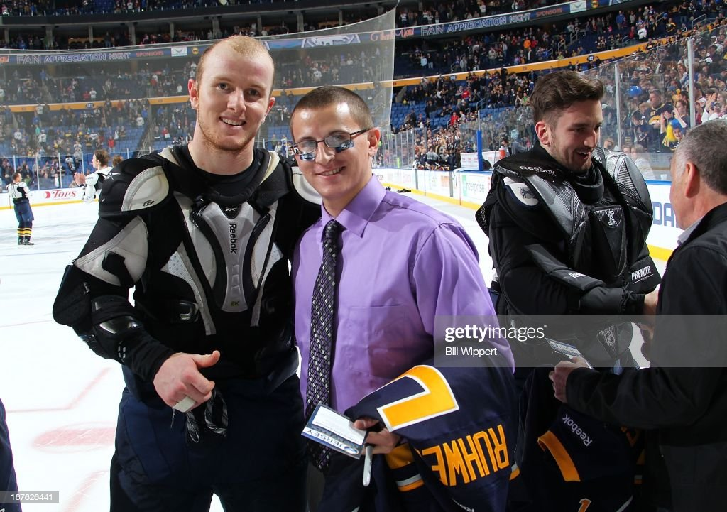 Chad Ruhwedel #5 of the Buffalo Sabres poses with a fan who received Ruhwedel's game jersey following a game against the New York Islanders on April 26, 2013 at the First Niagara Center in Buffalo, New York. The Sabres defeated the Islanders 2-1.