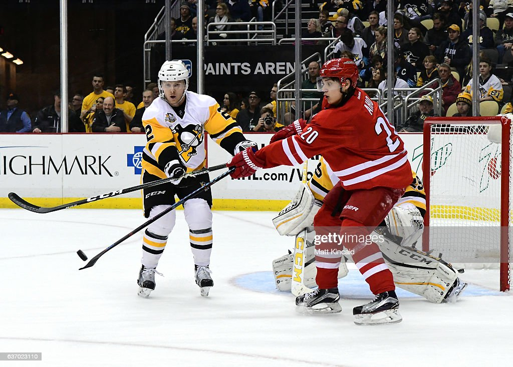 Chad Ruhwedel #2 of the Pittsburgh Penguins and Sebastian Aho #20 the Carolina Hurricanes reach for the puck at PPG PAINTS Arena on December 28, 2016 in Pittsburgh, Pennsylvania.