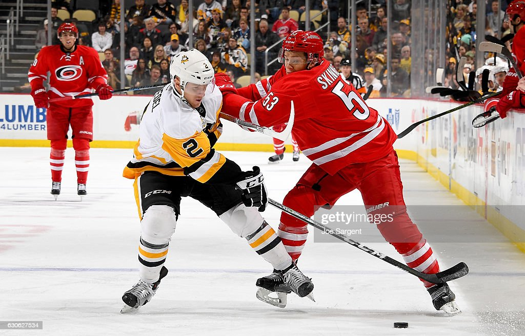 Chad Ruhwedel #2 of the Pittsburgh Penguins handles the puck against Jeff Skinner #53 of the Carolina Hurricanes at PPG Paints Arena on December 28, 2016 in Pittsburgh, Pennsylvania.