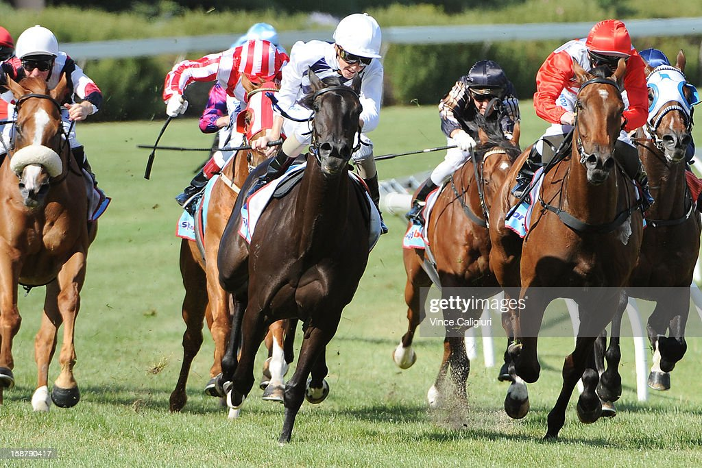 Chad Schofield riding Hidden Message (ctr) wins the Late Starter Membership Handicap during Melbourne racing at Moonee Valley Racecourse on December 29, 2012 in Melbourne, Australia.