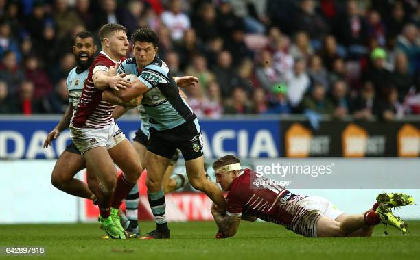 Chad Townsend of CronullaSutherland Sharks is tackled by Sam Powell of Wigan Warriors during the Dacia World Club Challenge match between Wigan...