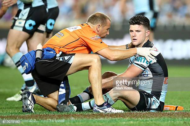 Chad Townsend of the Sharks is attended to by a trainer during the 2016 NRL Grand Final match between the Cronulla Sharks and the Melbourne Storm at...