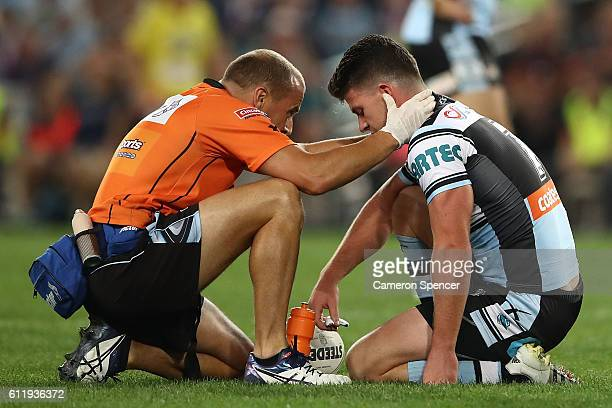 Chad Townsend of the Sharks is attendted to by a trainer after a high tackle during the 2016 NRL Grand Final match between the Cronulla Sharks and...