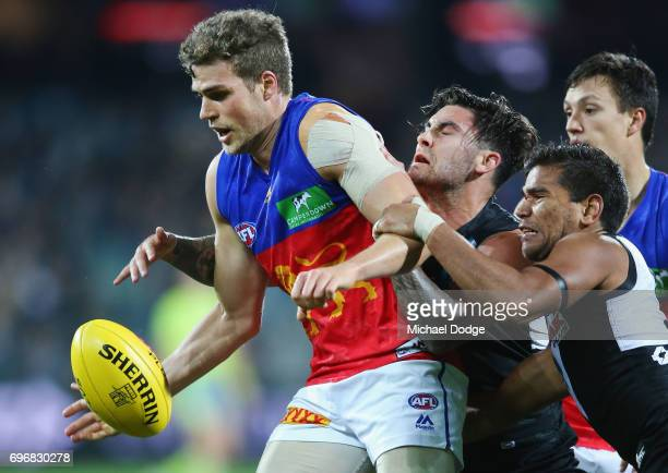 Chad Wingard and Jake Neade of the Power tackled Jarrod Berry of the Lions during the round 13 AFL match between the Port Adelaide Power and the...