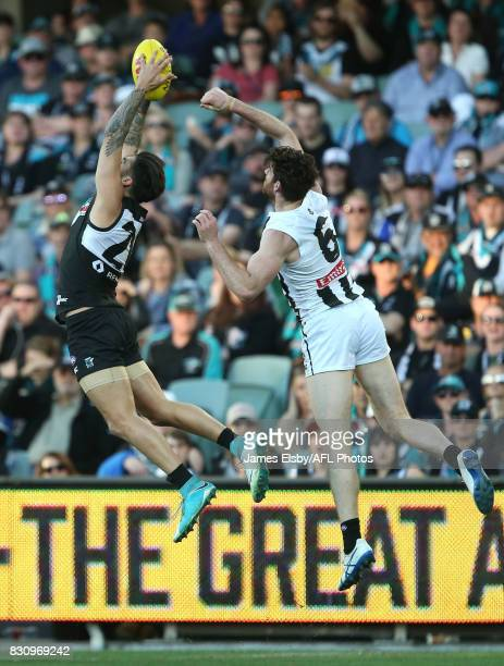 Chad Wingard of the Power flies with Tyson Goldsack of the Magpies during the 2017 AFL round 21 match between the Port Adelaide Power and the...