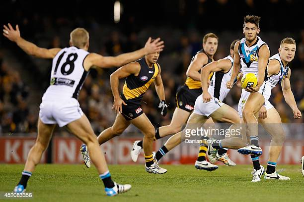 Chad Wingard of the Power looks to handball to tea mate Kane Cornes during the round 17 AFL match between the Richmond Tigers and the Port Adelaide...