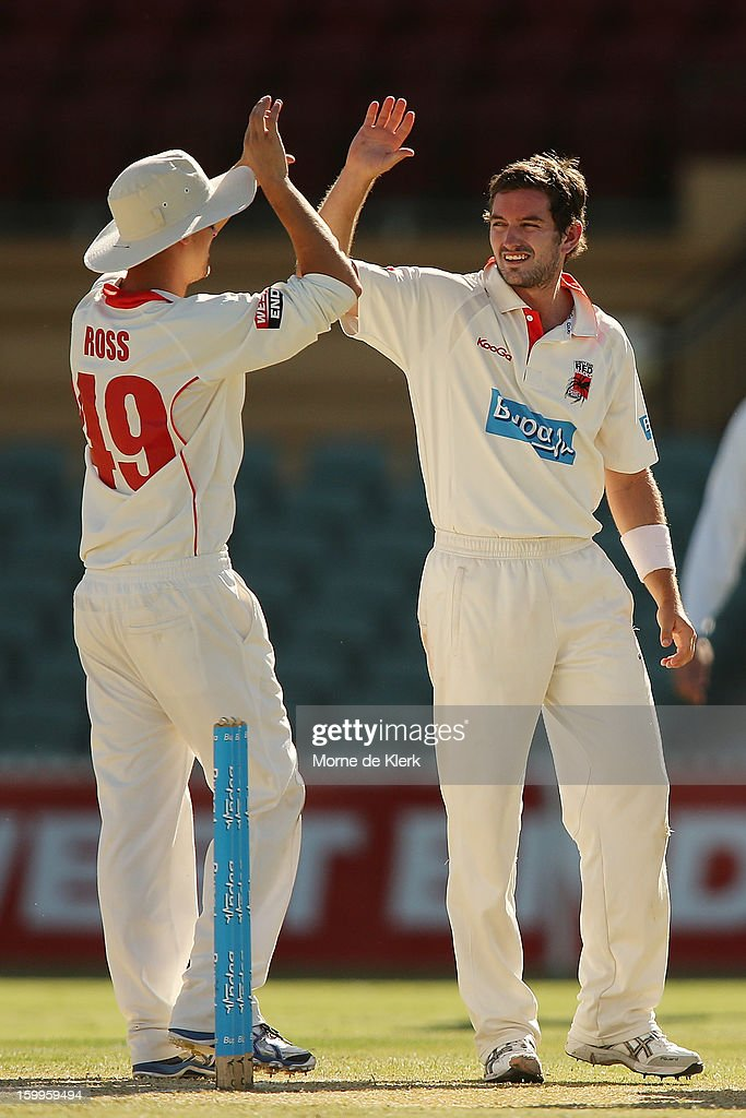 Chadd Sayers (R) of the Redbacks celebrates after getting the wicket of Chris Rogers of the Bushrangers during day one of the Sheffield Shield match between the South Australia Redbacks and the Victoria Bushrangers at Adelaide Oval on January 24, 2013 in Adelaide, Australia.