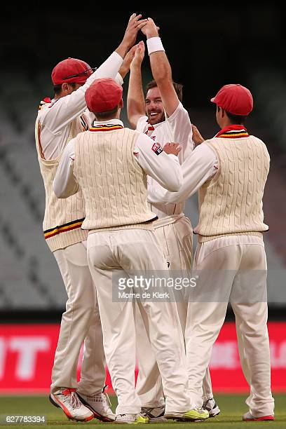 Chadd Sayers of the SA Redbacks celebrates with teammates after getting the wicket of Peter Nevill of the NSW Blues during day one of the Sheffield...