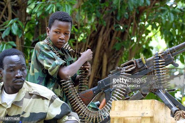 A Chadian child soldier stands in front of a machine gun 24 March 2003 at De Roux camp in Bangui Central Africa where stolen objects and arms are...