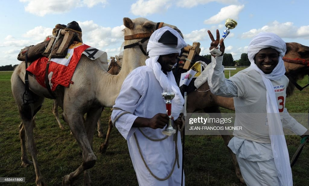 Chadian Hissein Wiledah (R) and Tahir Alladani wave after the second place during French Cup of camel races on August 10, 2014 on the horserace track of La Chartre-sur-le-Loir, western France. Unusual in these latitudes, eight dromaderies that have never seen the desert, took part in two races of 1000 meters.