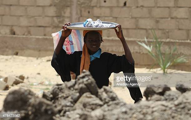 N'DJAMENA CHAD JUNE 22 A Chadian kid holds a tray on the top of his head at a slumdog of N'djamena Chad on June 22 2015 Referred to as the 'Dead...