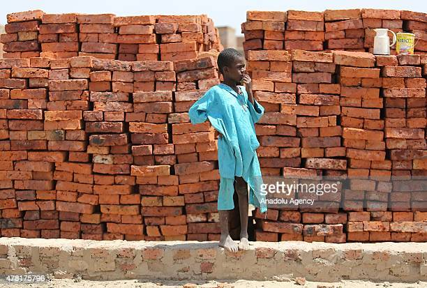 N'DJAMENA CHAD JUNE 22 A Chadian kid standing next to stacked bricks in a village near the capital N'Djamena Chad on June 22 2015 Turkeys...