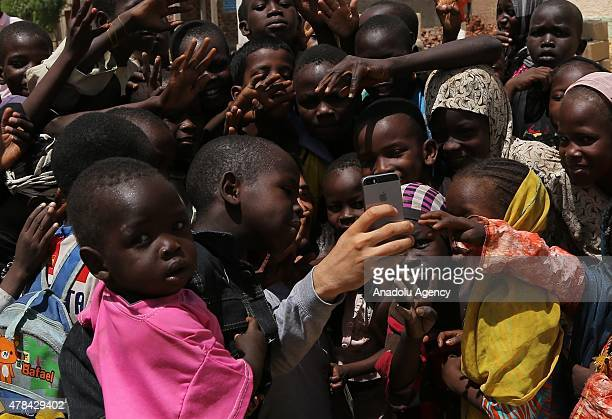 N'DJAMENA CHAD JUNE 22 Chadian kids pose for a selfie with a man at a slumdog of N'djamena Chad on June 22 2015 Referred to as the 'Dead Heart of...